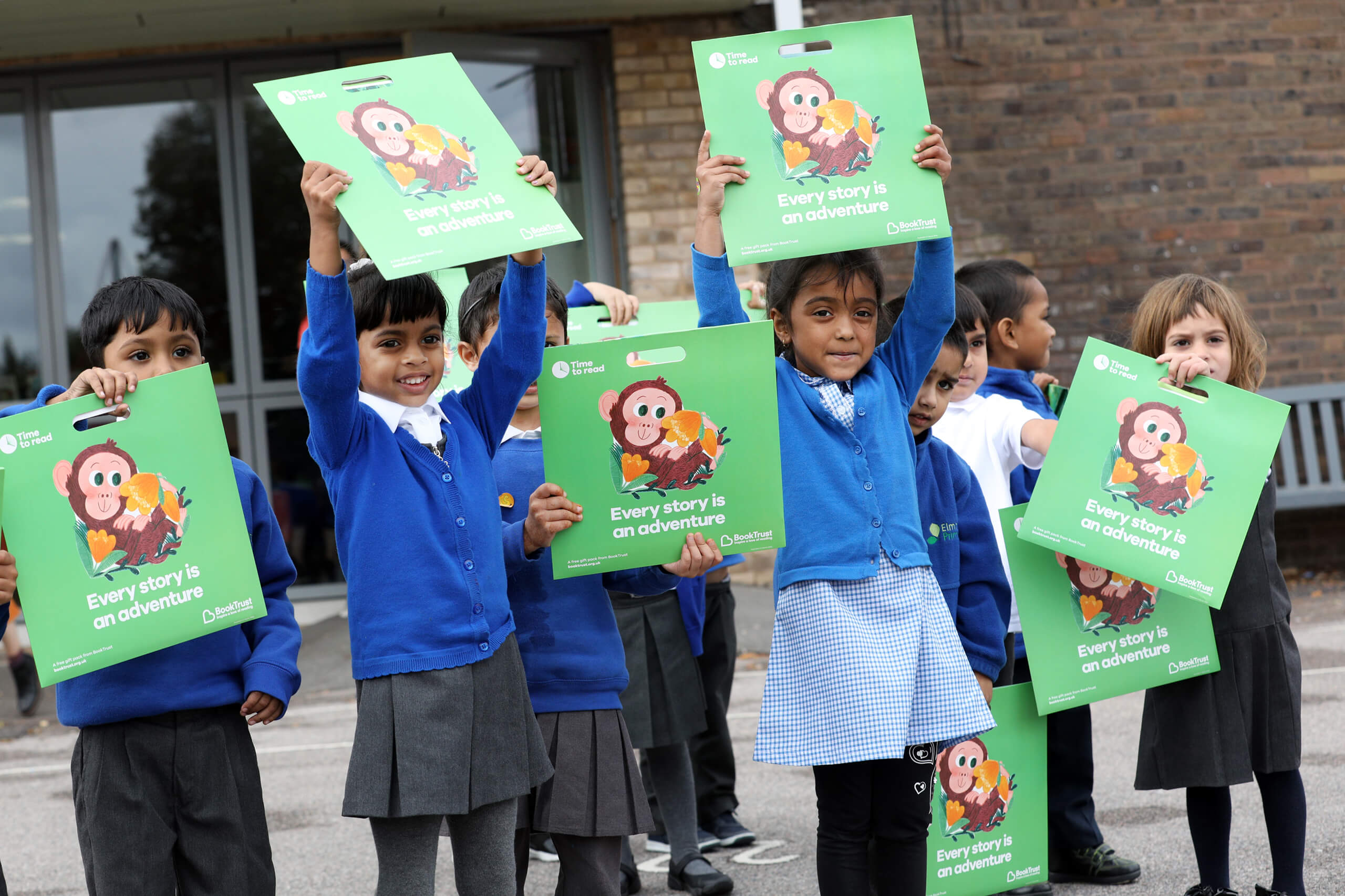 Children holding up Little Monkey by Marta Altes at Elmhurst primary school in Newham